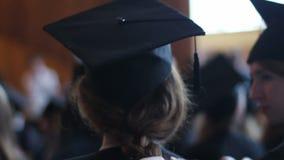 Het haar van de dochter van het moedervlechten Voorbereidingen voor graduatieceremonie bij universiteit stock footage