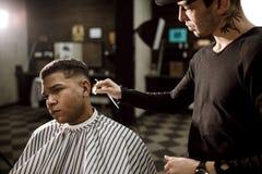 Het haar van de kappersschaar aan de kanten voor een modieuze zwart-haired mens in de herenkapper Mensen` s manier en stijl stock afbeeldingen