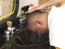 Het haar van de kapperwas aan de mens na kapsel in kapperswinkel stock foto's