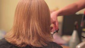 Het haar van de vrouw van kappersbesnoeiingen stock videobeelden