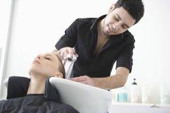 Het Haar van kapperwashing client bij Woonkamer stock foto's