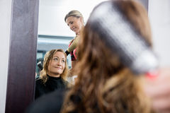 Het Haar van kapperworking on client in Salon stock afbeelding