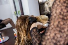 Het Haar van schoonheidsspecialiststyling client in Salon royalty-vrije stock fotografie