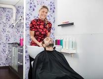 Het Haar van zekere Schoonheidsspecialistwashing male customer royalty-vrije stock afbeelding