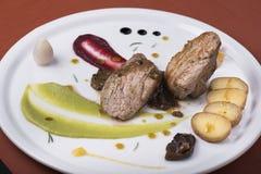 Het haasbiefstuk met pepersaus, stroopte aardappels en twee verschillende plantaardige puree 10 Stock Foto's