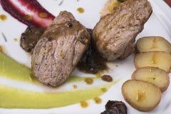 Het haasbiefstuk met pepersaus, stroopte omhoog geschotene aardappels en twee verschillende plantaardige puree 18close Stock Foto
