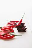 Het hakken van donkere chocolade met verse roodgloeiende Spaanse peperpeper Stock Foto