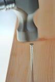 Het hameren van spijker in plank Stock Afbeelding