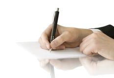 Het in hand schrijven van de pen op de witte pagina Stock Afbeeldingen