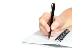 Het in hand schrijven van de pen op het notitieboekje Stock Foto