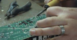 Het hand solderen van elektronische componenten op een raad stock videobeelden