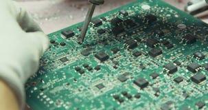 Het hand solderen van elektronische componenten op een raad stock video