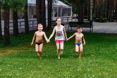 Het hand in hand in werking gestelde meisje en de twee jongens royalty-vrije stock foto
