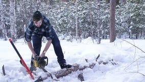 Het hand zagende hout van de houthakkerskettingzaag in het de winter sneeuwbos stock video