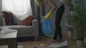 Het handbediende schot van Jonge vrouw doet het schoonmaken in de woonkamer na de partij stock video