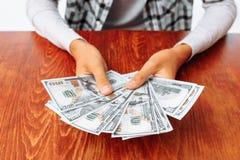 Het handenclose-up die heel wat honderd dollars houden factureert, op de achtergrond van een houten lijst, het verdiende geld stock afbeeldingen