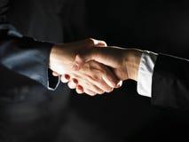 Het Handenschudden en het licht van de handdruk Stock Afbeelding
