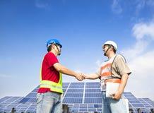 Het handenschudden van ingenieurs vóór zonnekrachtcentrale stock foto's