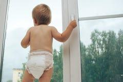 Het handvat van de babyholding van venster en het bekijken de straat royalty-vrije stock foto