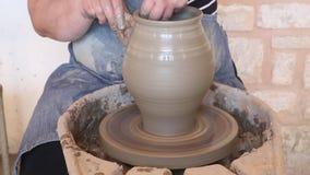 Het handwerk bij het maken van een vaas van klei op een aardewerkwiel stock video