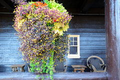 Het hangen het mandhoogtepunt van bloemen hangt vóór een oud houten hotel royalty-vrije stock foto