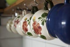 Het hangen op de koppen van de hakenkoffie in keuken Royalty-vrije Stock Afbeelding