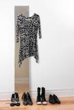 Het hangen van de kleding op een spiegel, en rij van schoenen Royalty-vrije Stock Afbeeldingen