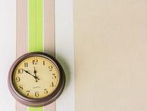 Het hangen van de klok op de muur stock fotografie