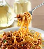 Het hangen van de spaghetti op een vork bij diner Stock Afbeeldingen