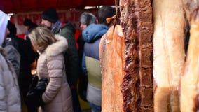 Het hangen van eigengemaakt droog varkensvlees met passers op de achtergrond, het festival van de varkensslachting stock videobeelden