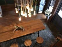 Het hangen van gloeilampen over lange houten koffietafel royalty-vrije stock foto's