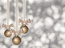 Het hangen van gouden Kerstmisballen met lint Stock Fotografie