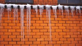 Het hangen van ijskegels op het dak van het gebouw en het sneeuwt stock video