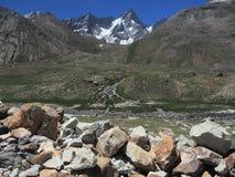 Het hangen van ijzige vallei in Zanskar: in de voorgrond zijn er vele morenekeien, achter een diepe woestijnvallei en hoge sneeuw Stock Fotografie