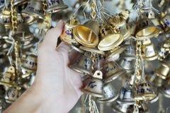 Het hangen van kleine gouden klokken voor geluk in Wat Pongarkad, Chachoengsao, Thailand Stock Afbeeldingen