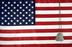 Het hangen van militaire hondmarkeringen op Amerikaanse vlag Stock Afbeelding