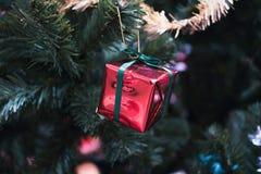 Het hangen van rode glanzende gift op Kerstmisboom Royalty-vrije Stock Foto's