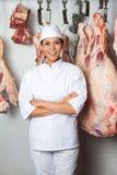 Het Hangen van slagersstanding against meat in Slachterij stock foto