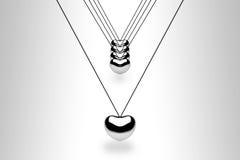 Het hangen van zilveren hartballen op wit Stock Foto