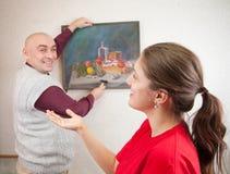 Het hangende beeld van het paar op muur bij. Nadruk op meisje Stock Fotografie
