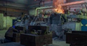 Het harde werk in de gieterij, arbeider het controleren ijzeruitsmelting in ovens, te hete en rokerige werkomgeving Metaal stock videobeelden