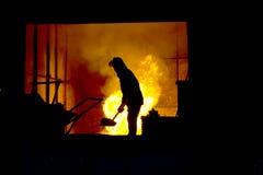 Het harde werk in een gieterij, smeltend ijzer stock foto's