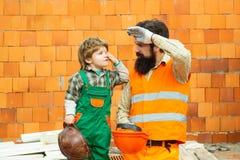 Het harde werk Werkdag Een team van bouwers is vermoeid op het werk Een mens en een jongen in een kostuum van bouwers stock fotografie