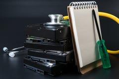 Het hardeschijfstation, de schroevedraaier, de stethoscoop en het notitieboekje voor tekst op zwarte achtergrond voor beschermen  royalty-vrije stock fotografie