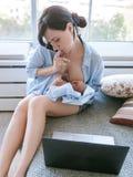 Het Hardworking moeder freelance zuigeling de borst geven stock afbeelding