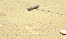 Het harken van het zand in de bunker Stock Foto's