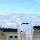 Het harken van sneeuw van dak Stock Foto's