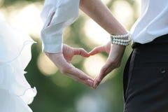 Het hart dat door handen van paar over zonsondergang wordt gemaakt Stock Fotografie
