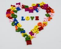 Het hart is gevoerd met houten multi-colored brieven en binnen het hart is de woordliefde Royalty-vrije Stock Fotografie