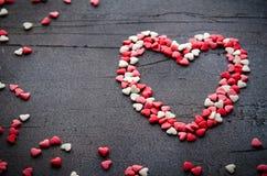 Het hart maakte met kleine suikergoedharten, roze, rode, witte kleuren, op donkere achtergrond Liefde, de dagconcept van Valentin Royalty-vrije Stock Foto